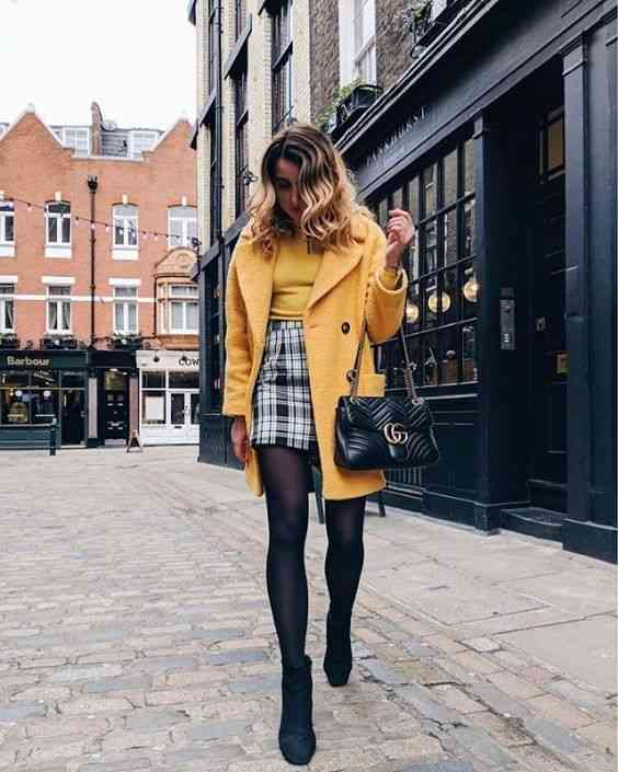 90s Outfits: yellow coat, yellow shirt, black and white plaid skirt, black tights, black booties, black handbag #outfit #yellow #blonde #trendy