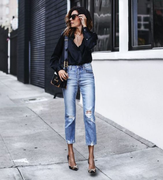 Date Night Outfits: black long sleeve v-neck ruffle blouse, ripped jeans, beige and black heels, black handbag, necklace, sunglasses #outfit #date #chic #black