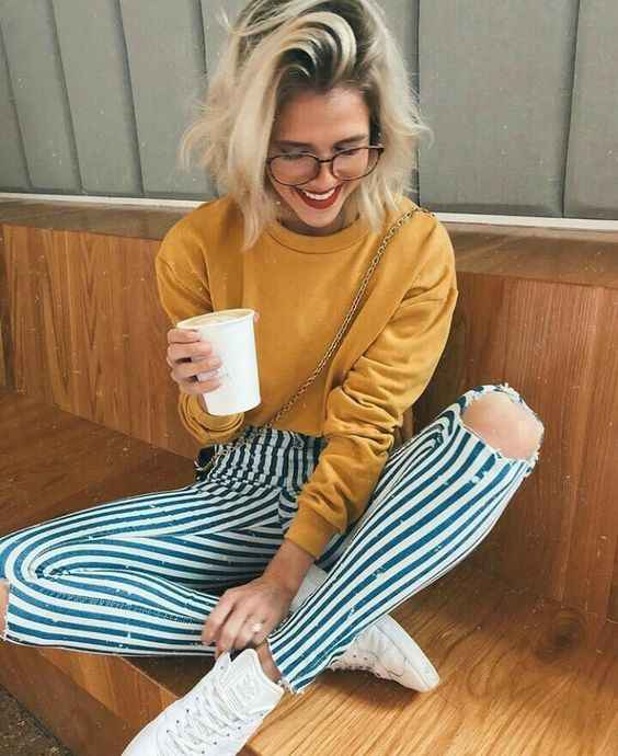 Hipster Outfit: yellow sweatshirt, blue and white striped ripped pants, white sneakers, crossbody bag #outfit #smile #glasses #blonde