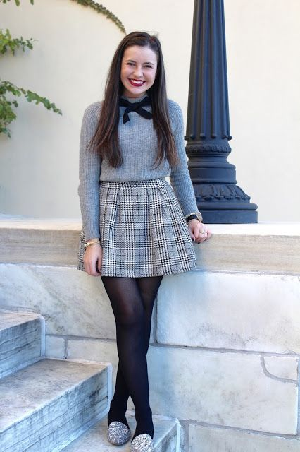 Preppy Outfits: gray sweater, black bow, gray and black plaid skirt, black tights, silver slip-on shoes, bracelets #outfitideas #makeup #longhair #brunette