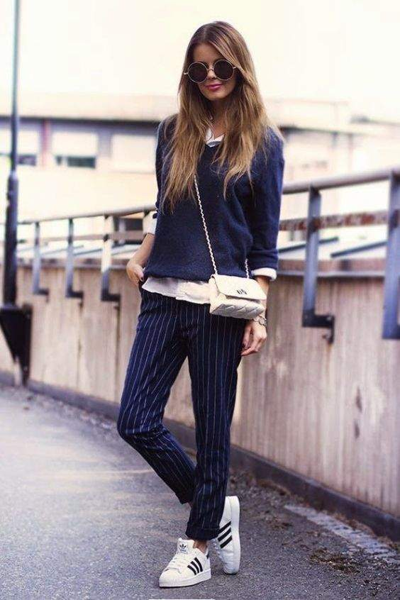 Preppy Outfit: navy blue sweatshirt, white shirt, navy blue and white striped pants, black and white sneakers, white crossbody bag, sunglasses #outfit #navyblue #college #fashion