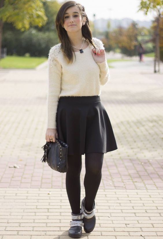 Preppy Outfit: beige sweatshirt, black circle skirt, black tights, black and silver booties, necklace, black purse #outfit #brunette #hairstyle #trendy