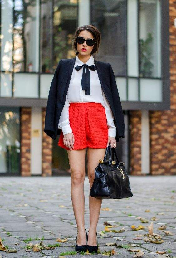Preppy Outfits: navy blue blazer, white bow front shirt, red high waisted shorts, black handbag, black heels, sunglasses #outfitoftheday #college #brunette #fashion