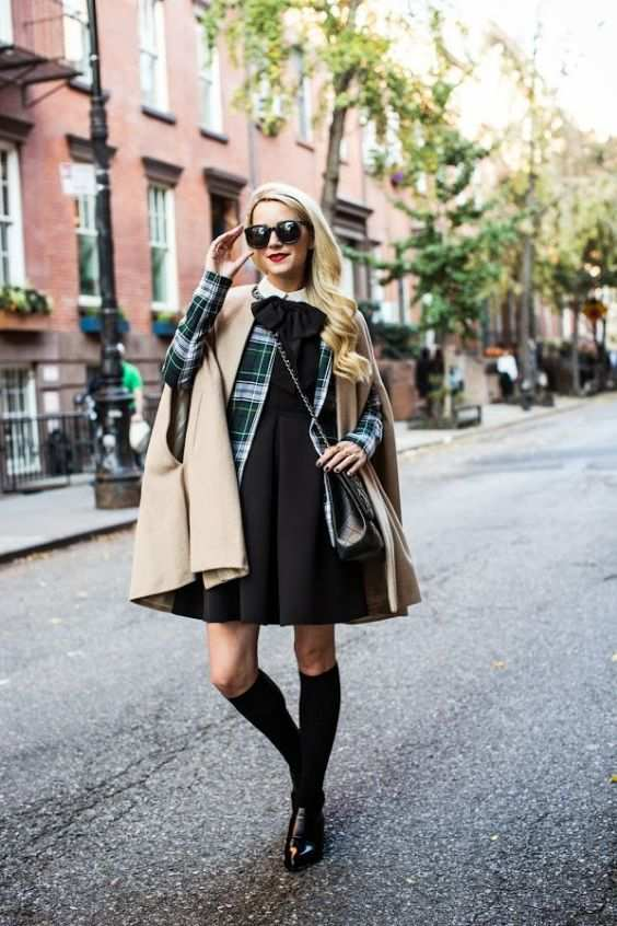 Preppy Outfit: beige coat, green plaid jacket, black bow front dress, knee high socks, black martens shoes, black crossbody bag, sunglasses #outfitoftheday #blonde #trendy #college