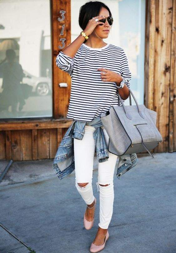 Preppy Outfit: black and white striped half sleeve top, white ripped jeans, baby pink ballerina flat shoes, bracelet, watch, denim jacket, gray handbag, sunglasses #outfitoftheday #brunette #woman #fashion