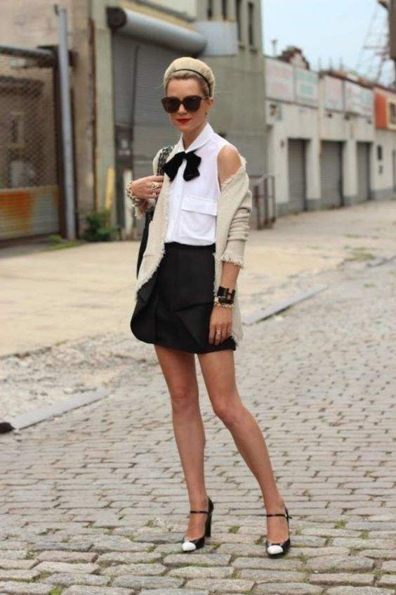 Preppy Outfits: white sleeveless shirt, black bow, black bubble skirt, black and white heels, beige cardigan, sunglasses , bracelets, black bag #outfit #college #fashion #girly