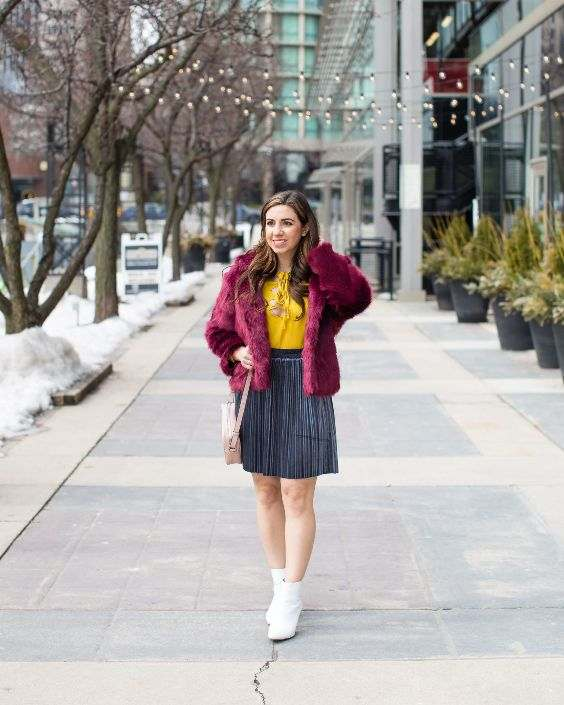 Winter Outfits: wine faux fur jacket, yellow shirt, gray pleated skirt, white booties, beige crossbody bag #outfit #brunette #snow #winter