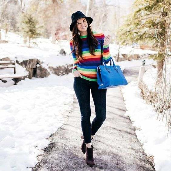 Winter Outfit: colorful sweater, black skinny jeans, brown booties, black hat, blue handbag #outfitoftheday #brunette #longhair #smile