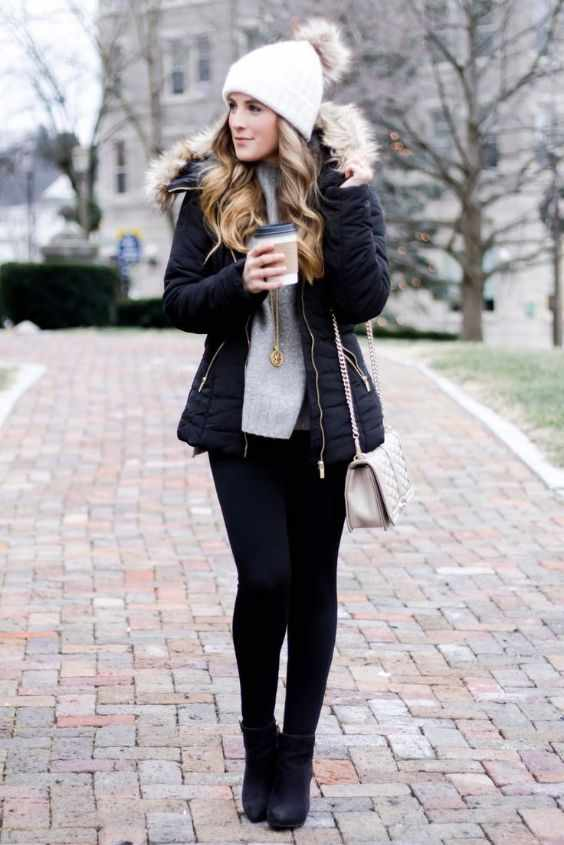 Winter Outfit: black jacket, gray sweater, black skinny pants, beige crossbody bag, white winter hat, black booties #outfit #winter #girl #blonde