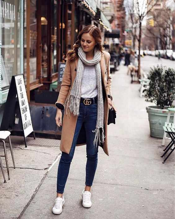 Winter Outfit: Light brown longline coat, white striped shirt, skinny jeans, gray scarf, white sneakers, black belt, black crossbody bag #outfitideas #women #trendy #snow